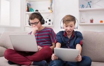 זוג ילדים צופים בטאבלטים